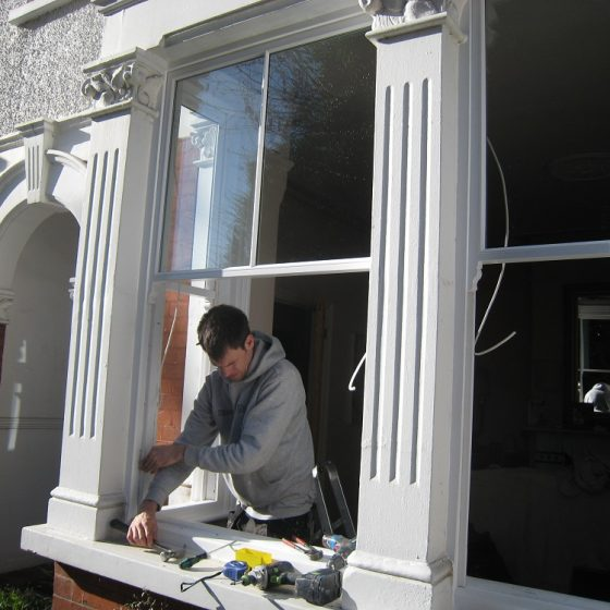 Man using a hammer on large window frames
