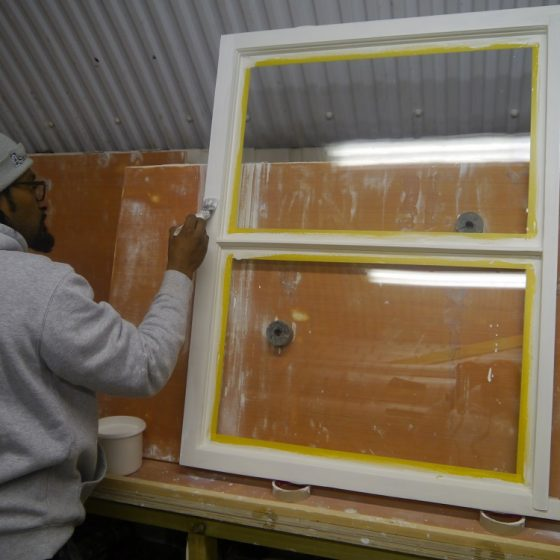 Man painting window frames inside of a workshop.