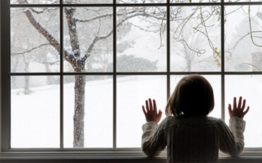 Young girl looking out of a sash window to snow outside.