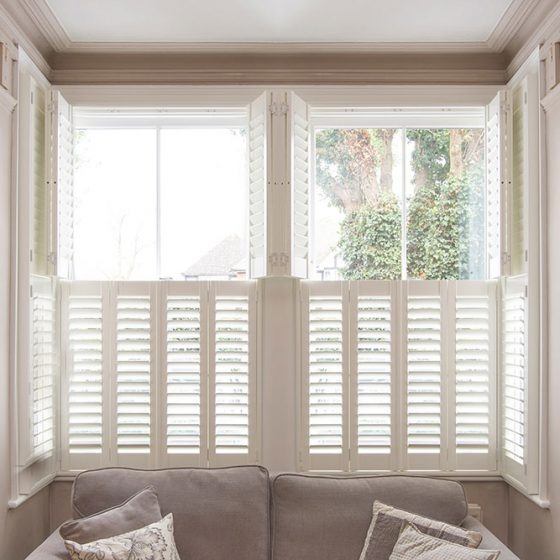 Lounge with couch and semi opened shutters on a sash window.