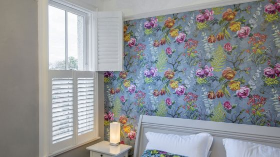 Colourful bedroom with Shutters half open.